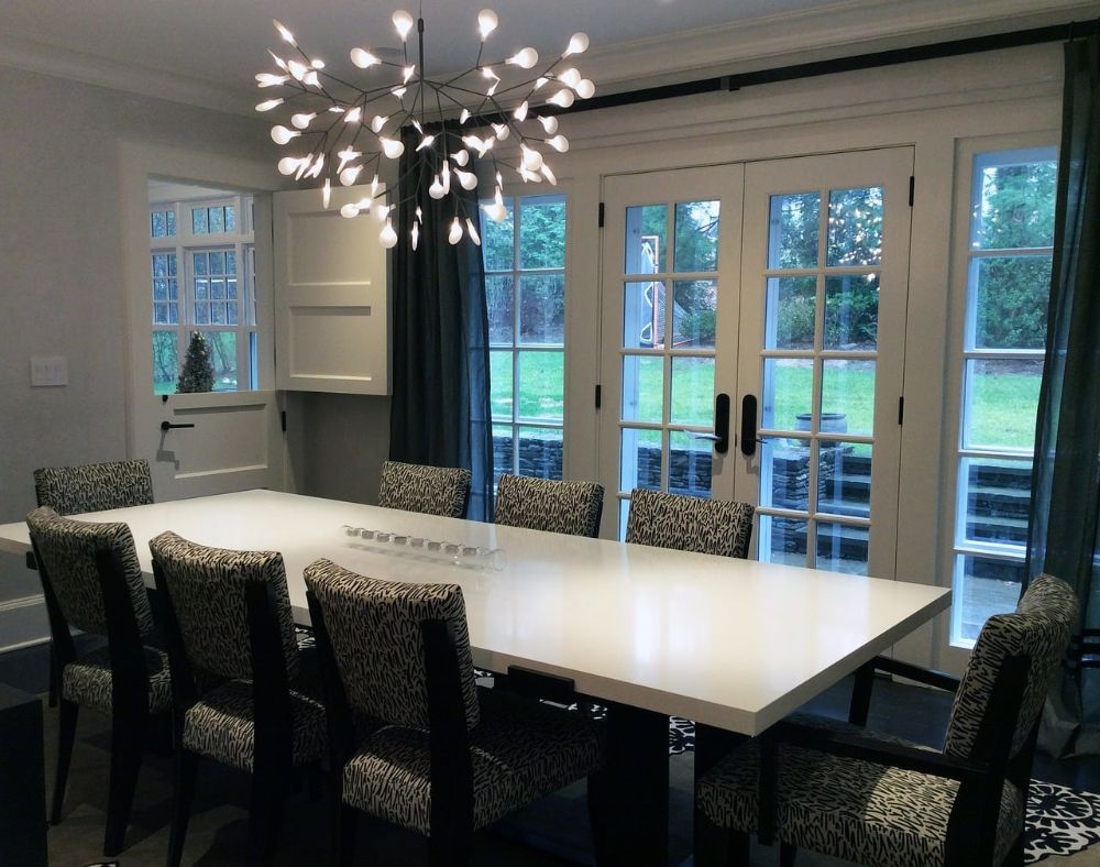 A dining room table with eight seats around it in a neat and new home.